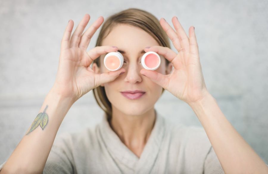 woman holding creams in front of her eyes